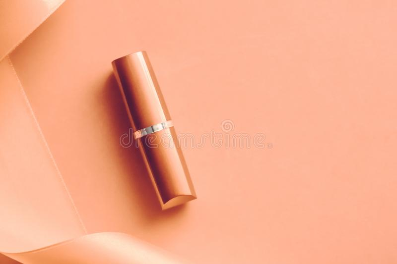 Luxury lipstick and silk ribbon on orange holiday background, make-up and cosmetics flatlay for beauty brand product design. Cosmetic branding, glamour lip gloss stock photos