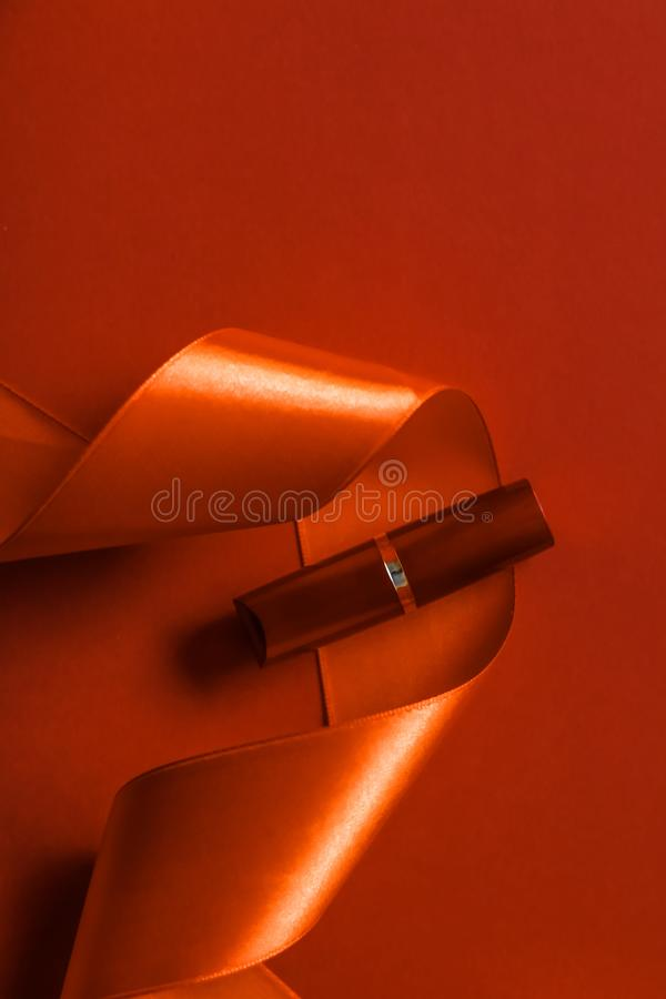 Luxury lipstick and silk ribbon on orange holiday background, make-up and cosmetics flatlay for beauty brand product design. Cosmetic branding, glamour lip gloss royalty free stock photos
