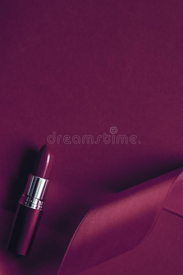 Luxury lipstick and silk ribbon on plum holiday background, make-up and cosmetics flatlay for beauty brand product design. Cosmetic branding, glamour lip gloss stock images