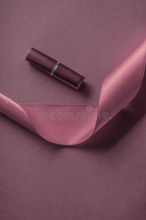 Luxury lipstick and silk ribbon on purple holiday background, make-up and cosmetics flatlay for beauty brand product design. Cosmetic branding, glamour lip gloss stock images