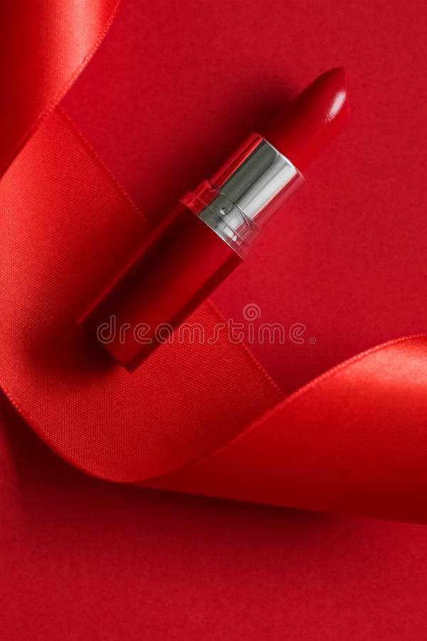 Luxury lipstick and silk ribbon on red holiday background, make-up and cosmetics flatlay for beauty brand product design. Cosmetic branding, glamour lip gloss stock photos