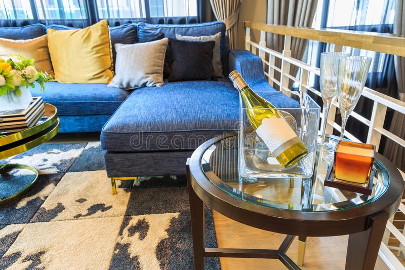 A luxury living room with blue sofa and a wine bottle on the tab royalty free stock photos
