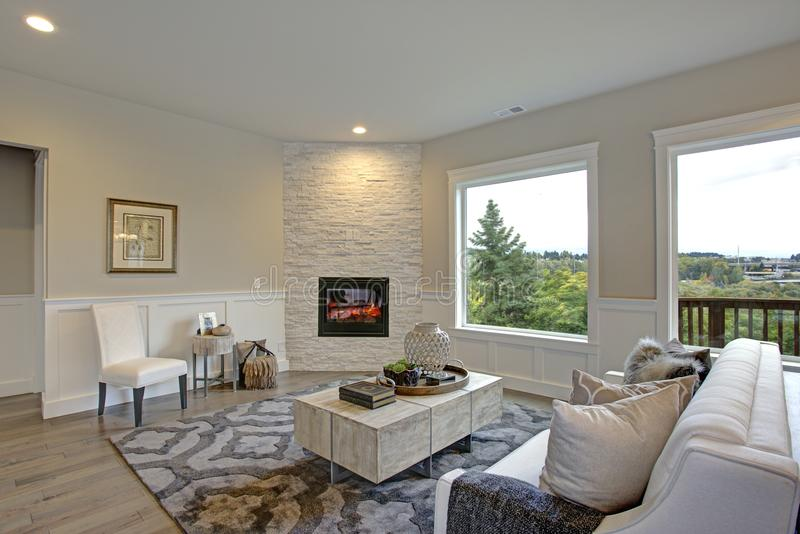 Luxury living room features corner stone fireplace. Relaxing white living room features corner stone fireplace lined with tan walls accented with lower wall stock image