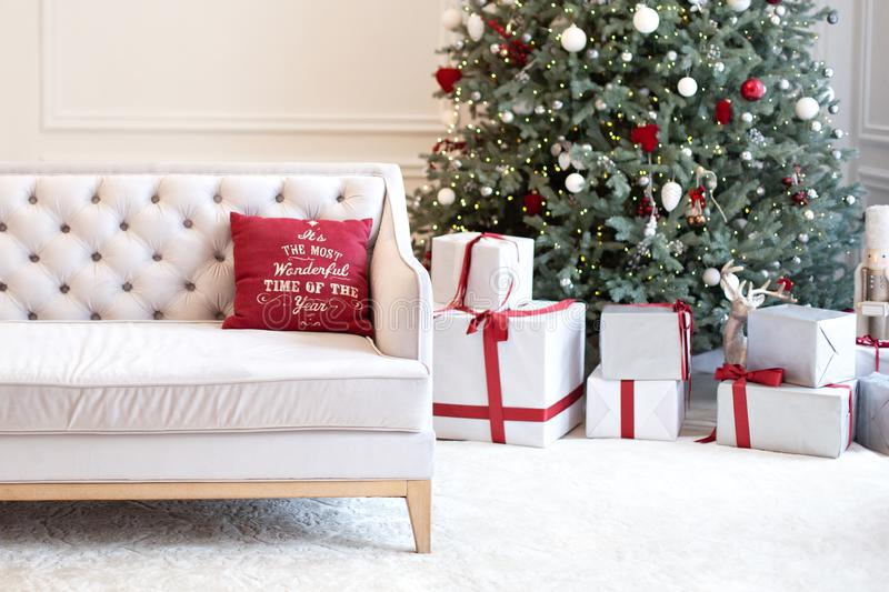 Luxury living room interior with sofa decorated chic Christmas tree, gifts and pillows. Classic interior in red shades. Christmas. At home. beige sofa on stock photos