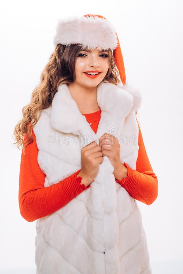 Luxury look for new year party. Pretty girl wear red santa hat and fur vest. Teenage model with fashion look. Little royalty free stock photo
