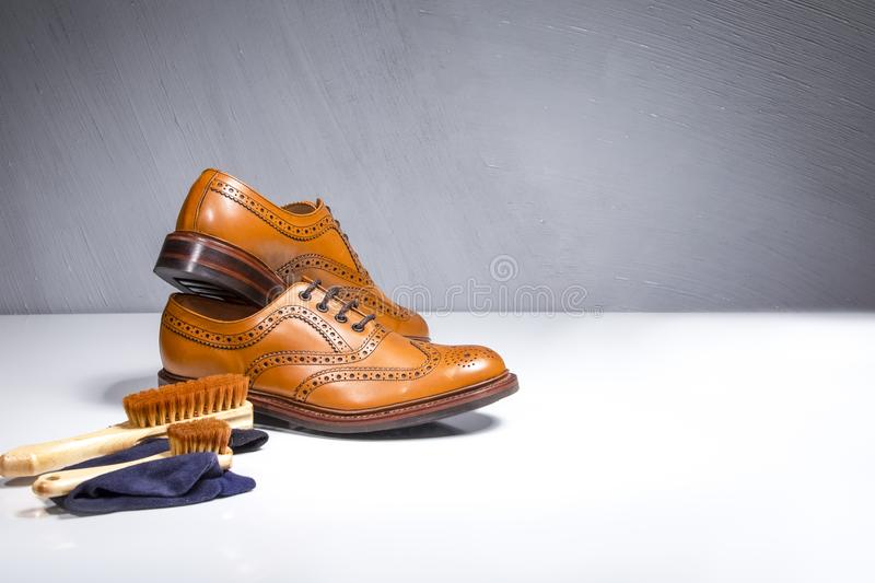 Luxury Male Tanned Full Broggued Oxford Calf Leather Shoes Along. With Cleaning Accessories and Cloth.Horizontal Image royalty free stock photo