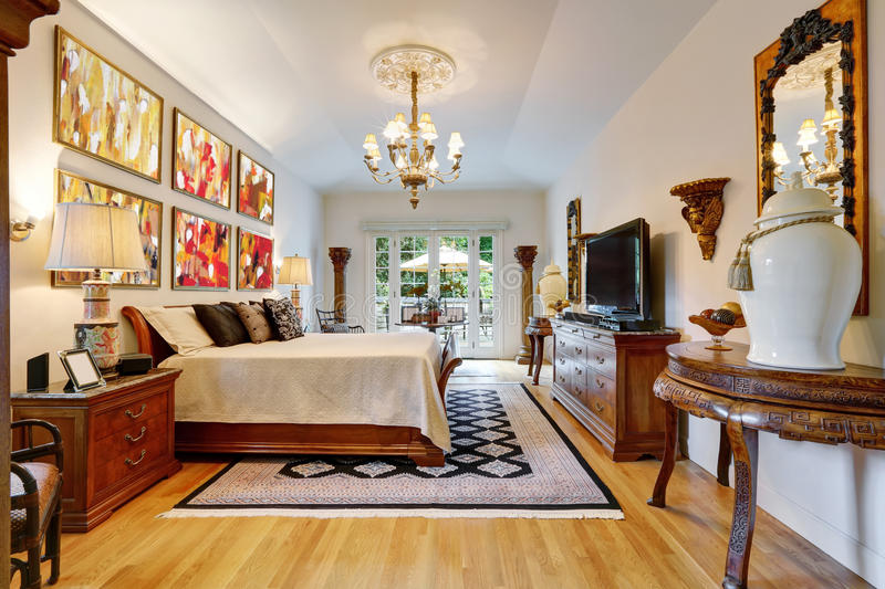 Luxury master bedroom interior with carved wooden furniture. Luxury large master bedroom interior with antique carved wooden furniture, king size bed, vintage royalty free stock images