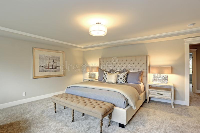 Luxury master bedroom interior . Luxury master bedroom interior furnished with two nightstands topped with stone and brass lamps, Large ivory cream tufted stock images