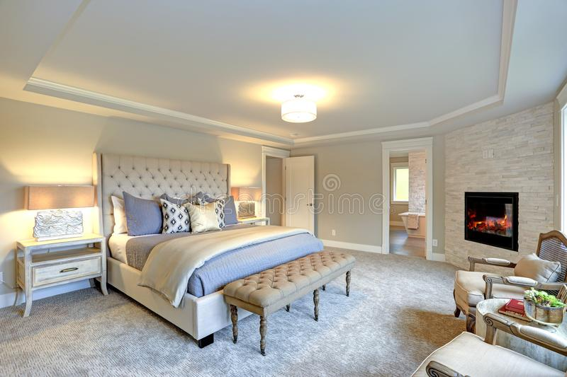 Luxury master bedroom interior . Luxury master bedroom interior furnished with two nightstands topped with stone and brass lamps, Large ivory cream tufted stock photography
