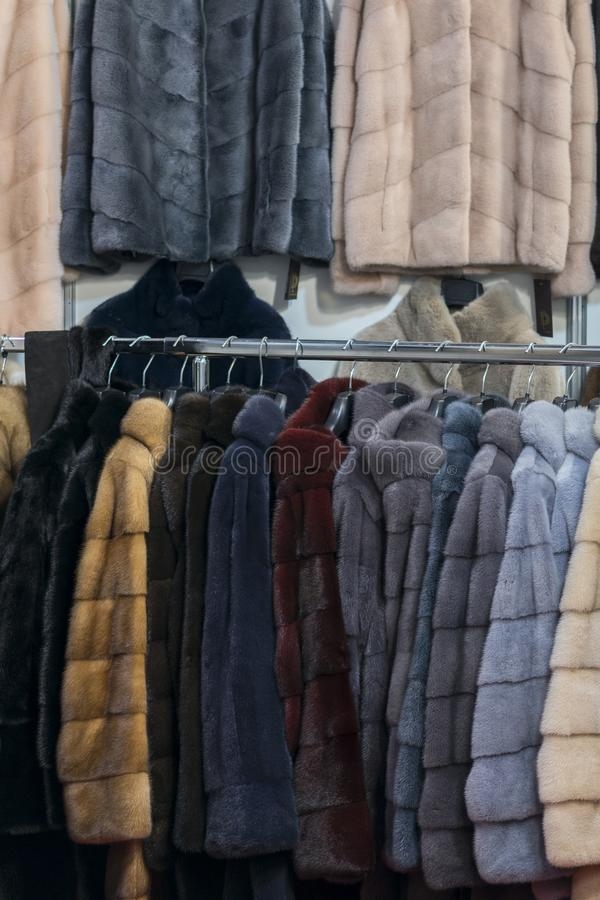 Luxury mink coats. Pink, grey, dark grey, pearl color fur coats on showcase of market. Best gift for a woman. Outerwear. Close up royalty free stock photos