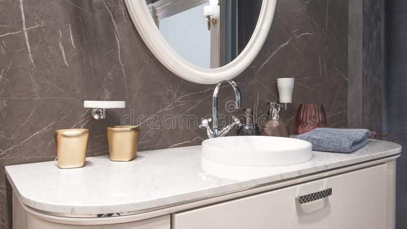 Luxury modern big white faucet mixer on a round sink in a beautiful beige marble bathroom, a large round mirror.  stock photos