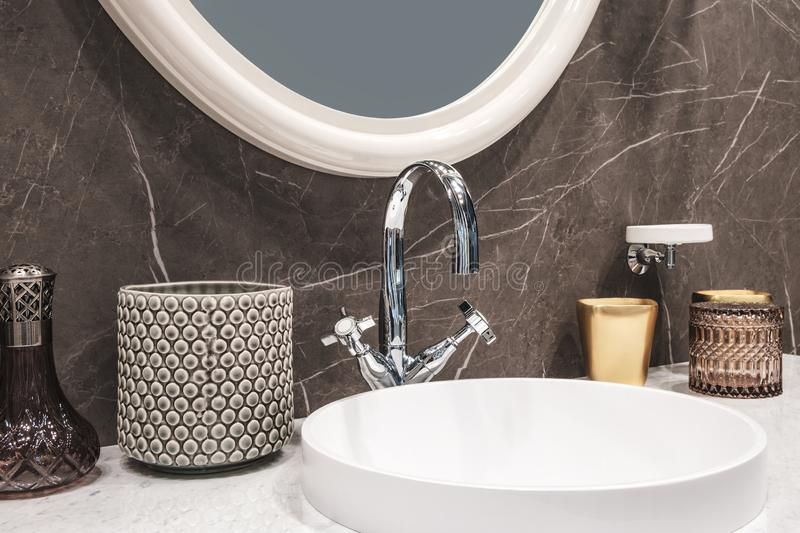 Luxury modern big white faucet mixer on a round sink in a beautiful beige marble bathroom, a large round mirror.  royalty free stock photo