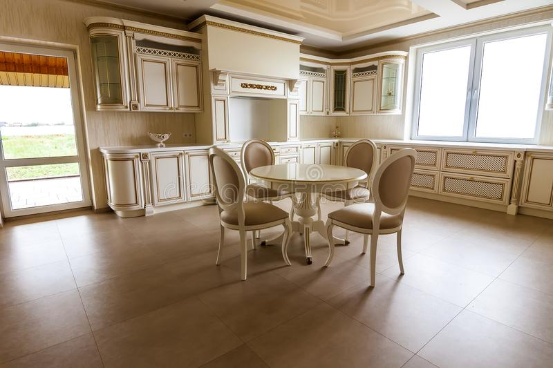 Luxury modern fitted kitchen interior. Kitchen in luxury home wi. Th beige cabinetry. Table and chairs royalty free stock photography
