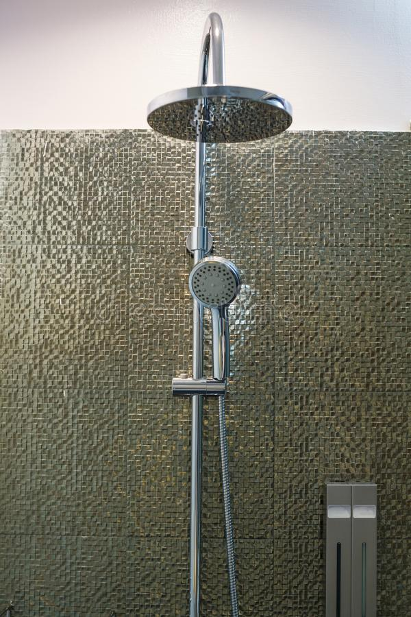 Luxury modern stainless steel ceiling rain shower, Shower head faucet and holder in bathroom on golden decorating tiles wall backg stock images