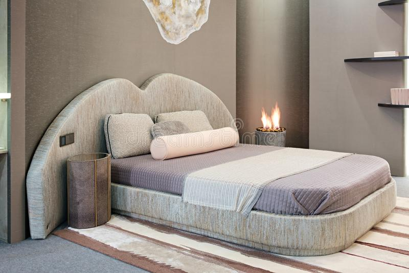 Luxury modern style bedroom, Interior of a hotel bedroom or private house or apartment with decorative fireplace with a flame.  royalty free stock image