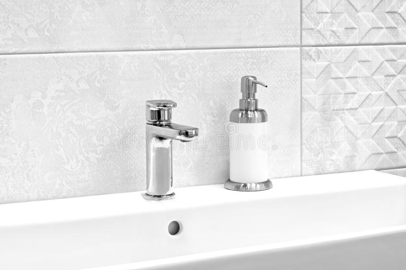 Luxury modern style faucet mixer and liquid soap on a white sink in a beautiful gray and white bathroom.  royalty free stock image