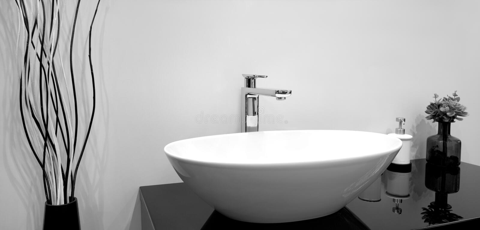 Luxury modern style faucet mixer on a white sink in a beautiful gray and white bathroom royalty free stock photography