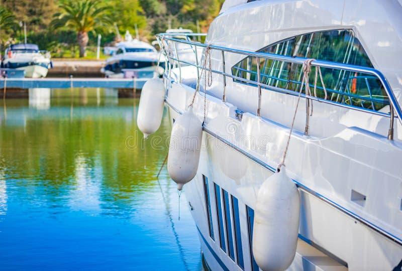 Luxury motor yacht boat anchoring at marina. Detail view of luxury motor yacht boat anchoring at harbor stock photo