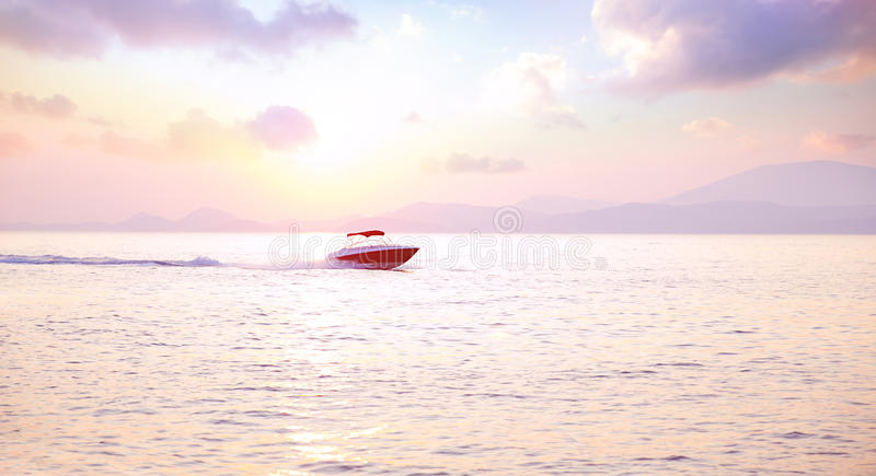Luxury motorboat. On the sea in mild pink sunset light, active lifestyle, expensive water transport, summer vacation, speed and freedom concept royalty free stock photos