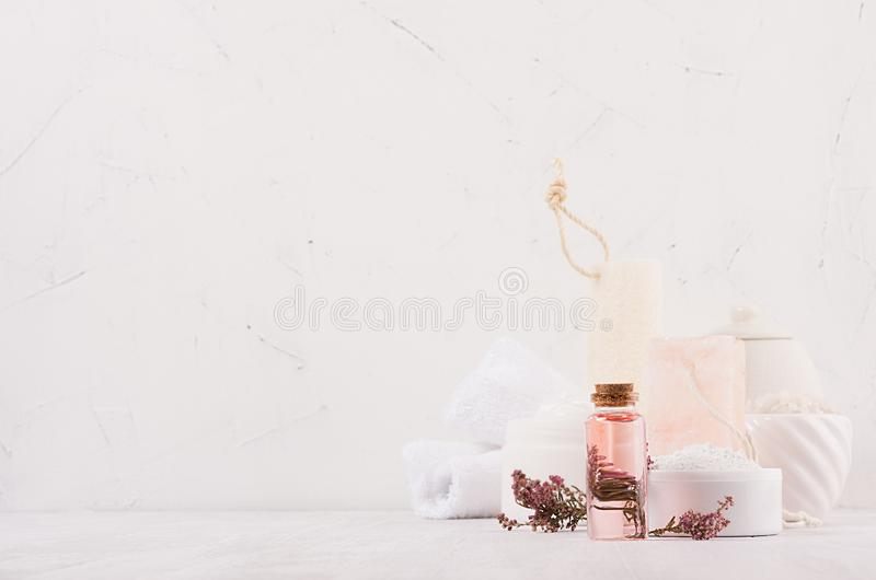Luxury organic body and skin care spa cosmetics collection, pink oil, flowers, natural bath accessories on white wood background. Luxury organic body and skin stock images