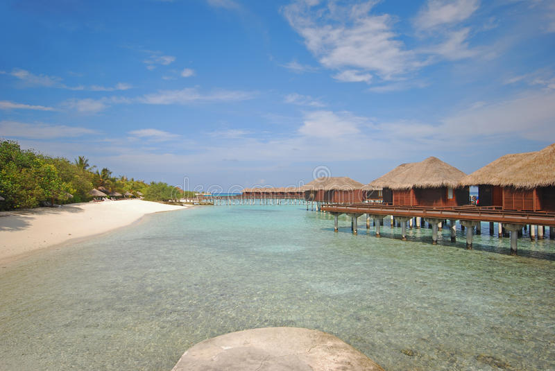 Luxury Overwater Villa connected to Beach with Platform. Luxury Overwater Villa connected to White Sandy Beach with Viewing Platform overlooking crystal clear stock photo