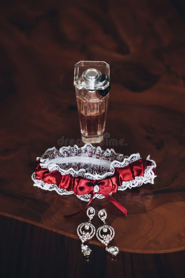 Luxury perfume bottle and garter on wooden table, bride boudoir. Set. morning preparation stock photo