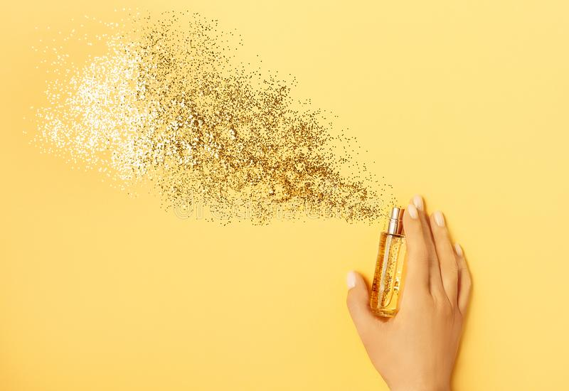Luxury perfume concept. Female hand holding stylish bottle of perfume with spray of sparkles on yellow background stock photography