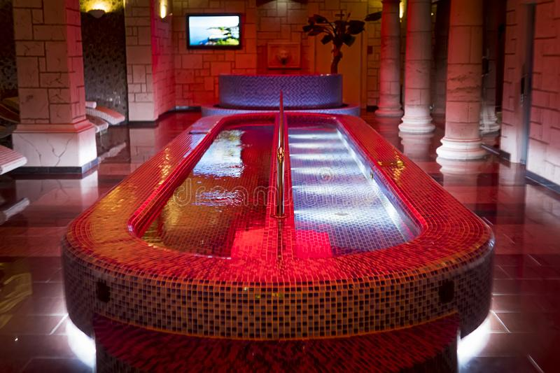 Luxury plunge pool in the centre of the column design spa. A filled spa pool in a pillared hall of dainty sauna. Indoor aquazone stock images