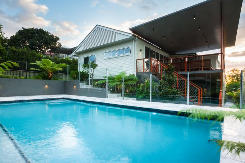 Luxury poolside closes up with modern house with green trees royalty free stock photography
