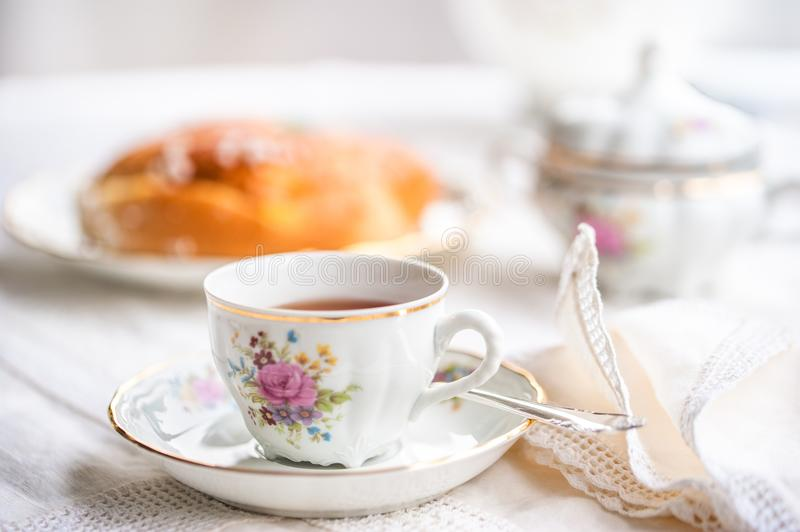 Luxury porcelain tea set with a cup, teapot, sugar bowl. On white tablecloth with spongy cake on a plate royalty free stock images