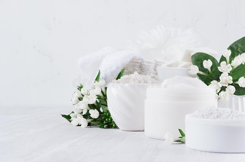 Luxury pure white cosmetics set of natural products for body and skin care - cream, salt, scrub and small flowers on white wood. Luxury pure white cosmetics set royalty free stock image