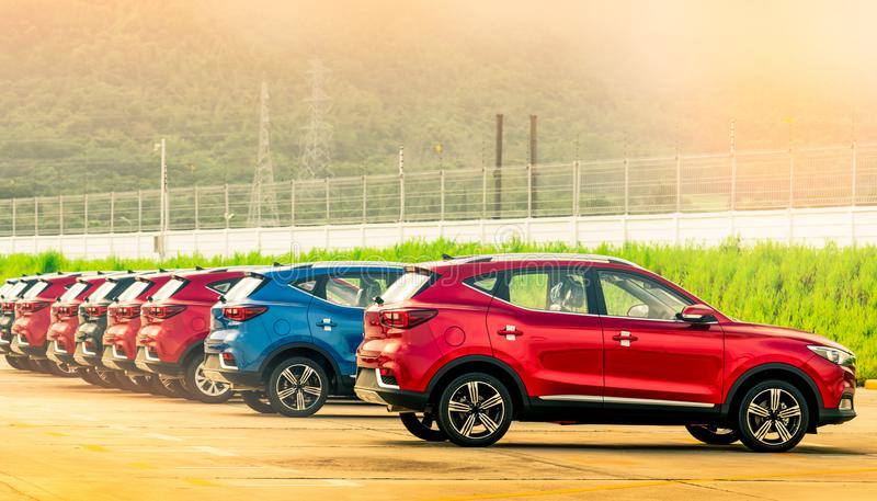 Luxury red, blue and black new suv car parked on concrete parking area at factory near fence of factory. Car stock for sale. Car factory parking lot stock image