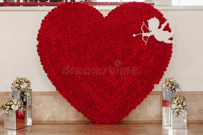Luxury red heart of roses and cupid with arrows at wedding reception, special photo booth zone. expensive wall arrangements of de. Corations at wedding ceremony stock image