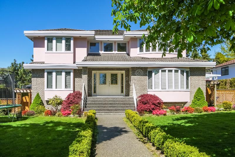Luxury residential house with neatly decorated front yard. Big family house with concrete pathway to the entrance and tree shadow royalty free stock photos
