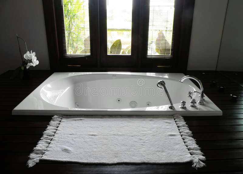 Luxury resort hotel bathroom. A photograph showing the white sunken bath tub in a luxurious hotel resort bathroom. Interior beautifully finished with dark black stock image