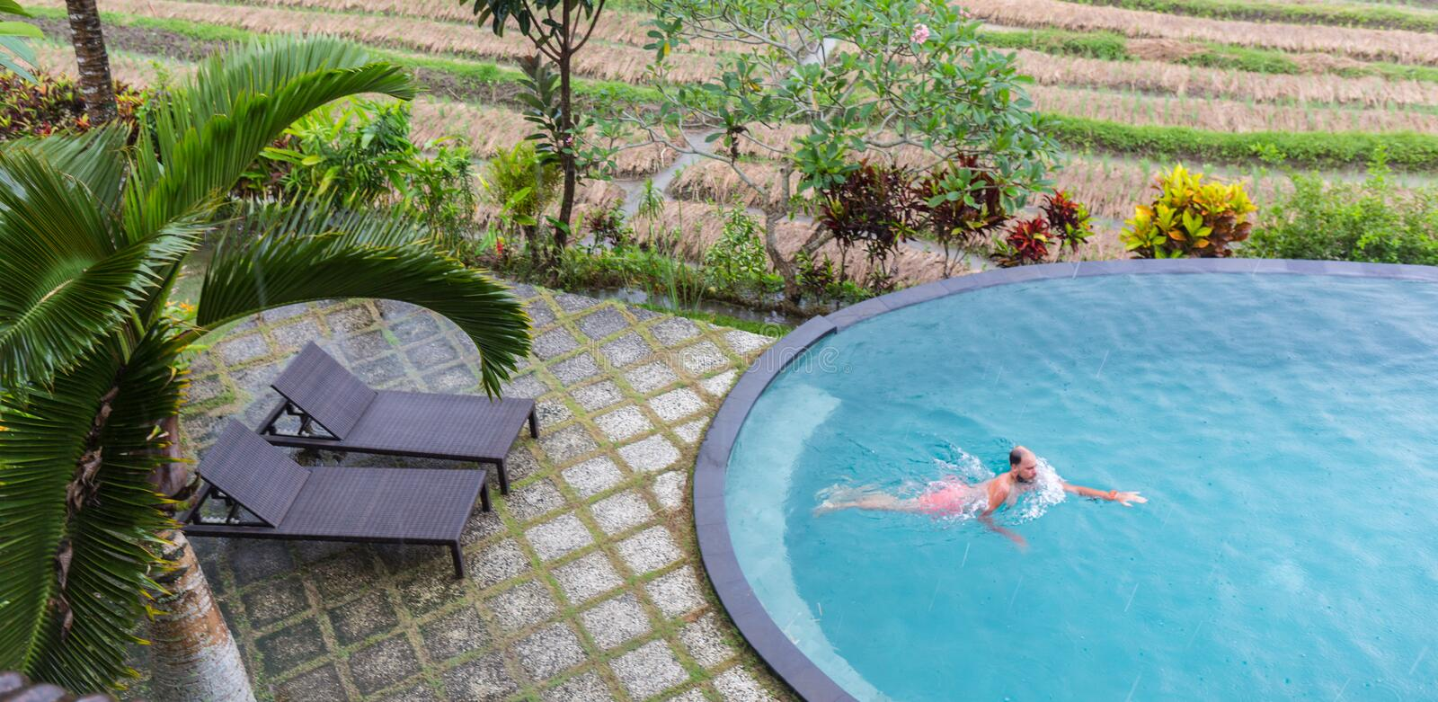 Luxury Resort. Man Relaxing In Infinity Swimming Pool Water. Beautiful Happy Healthy Male Model Enjoying Summer Travel stock images