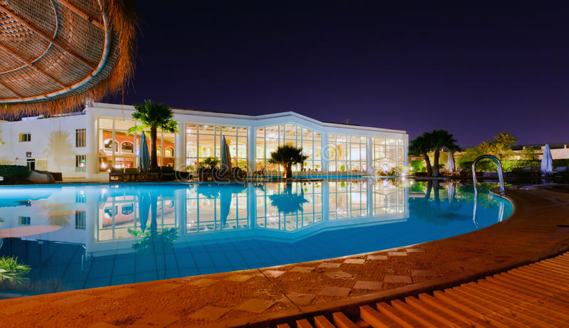 A luxury resort at night. A luxury resort with a pool, captured in the evening royalty free stock photos