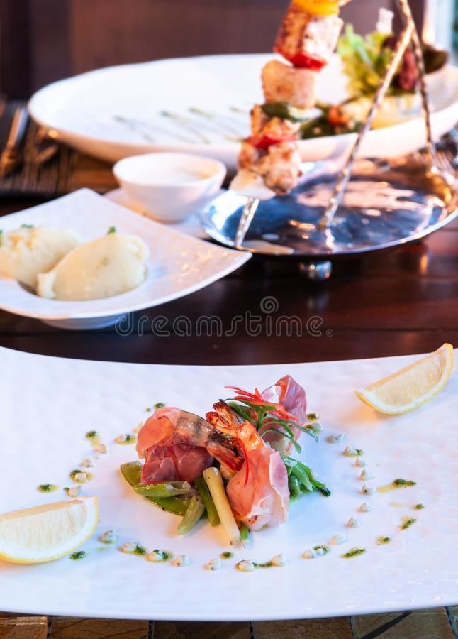 Luxury resort restaurant dinner table setting with barbecue and royalty free stock image