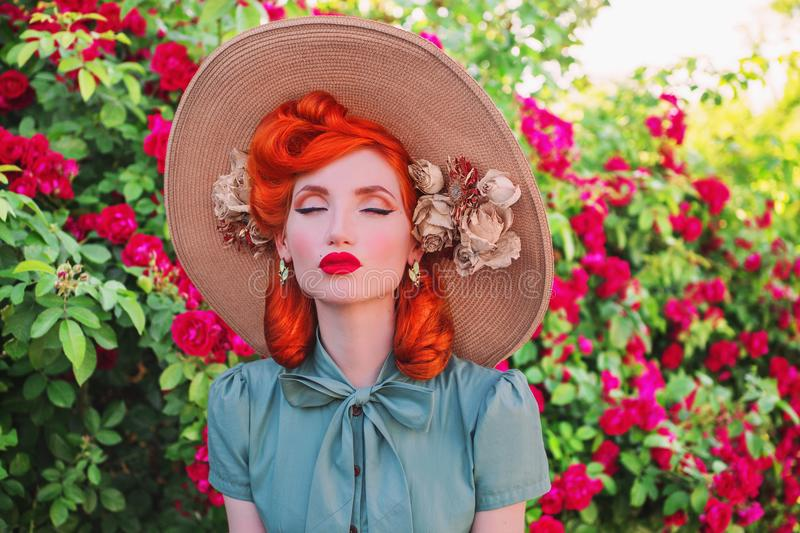 Luxury retro girl with red lips in mint dress on a beautiful flower summer background. Young redhead model in a hat with flowers stock photos