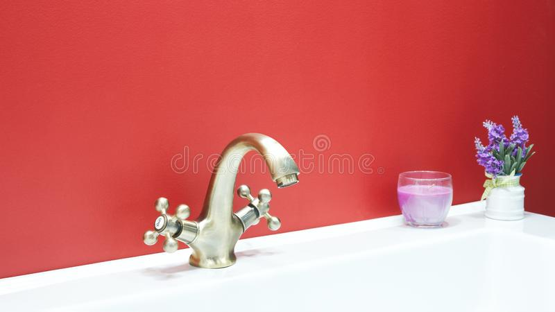 Luxury retro style bronze faucet mixer on a white sink in a beautiful red bathroom.  royalty free stock photos
