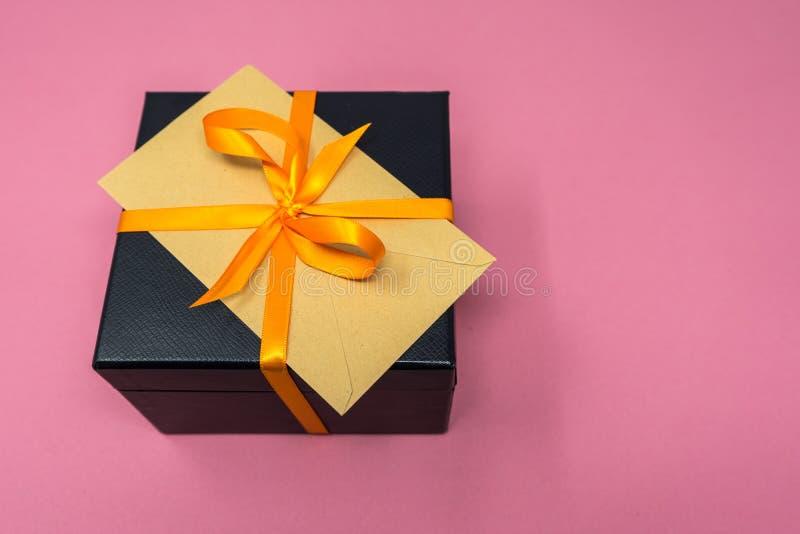 Luxury Ribboned Black Cube Gift Box, Orange Ribbon with Envelop on Top.  royalty free stock image