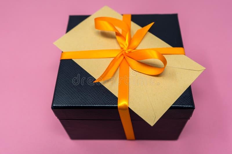Luxury Ribboned Black Cube Gift Box, Orange Ribbon with Envelop on Top.  royalty free stock photos