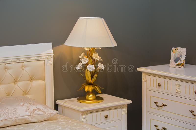 Luxury royal white bedroom in antique style. Bedside table with a chic lamp.  stock images
