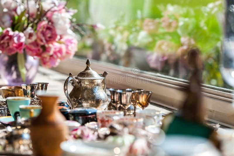 Luxury set of silver and porcelain dish with flowers. In front of window in vintage interior stock photo