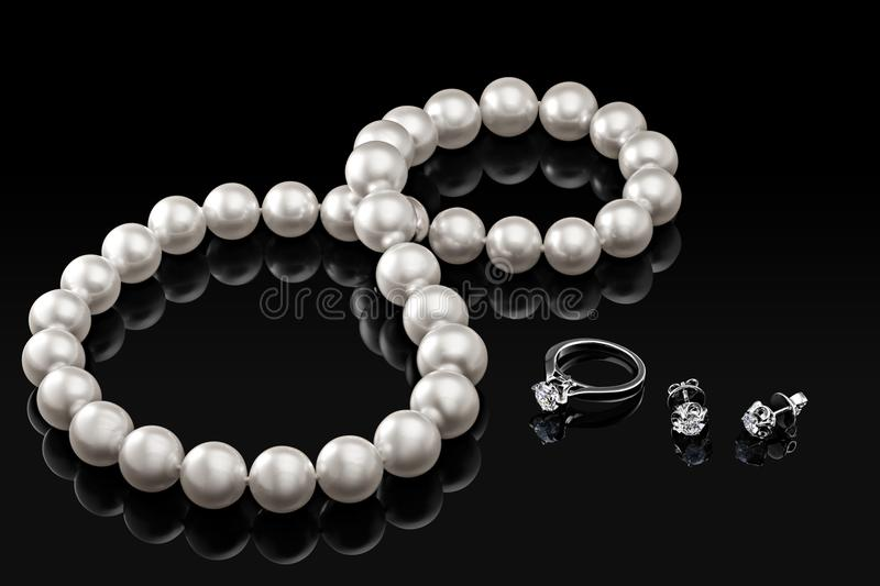 Luxury set white pearl necklace and jewelry with diamonds in ring and earrings on a black background. With glossy reflection and blank template for your design stock photography