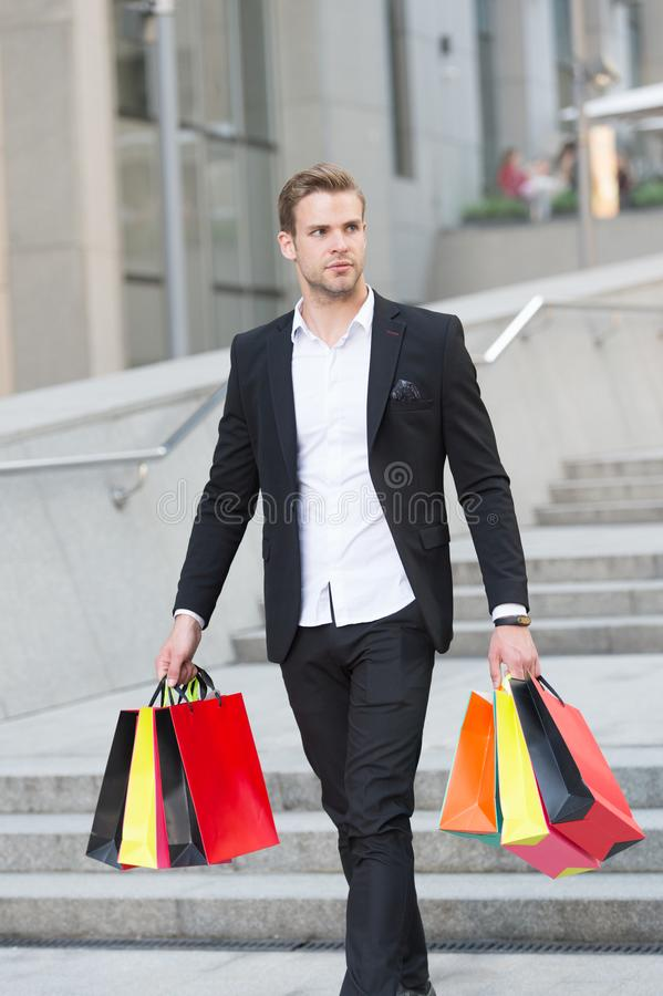 Luxury shopping. Boutique gallery client. Man shopper carries shopping bags urban background. Successful businessman royalty free stock photos