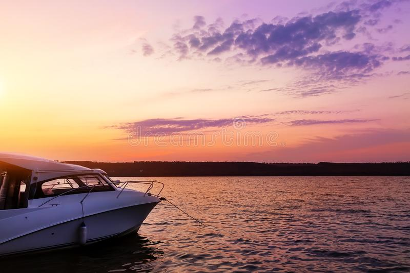 Luxury small fishing motorboat moored near lake or river coast at scenic evening with beautiful dramatic vibrant suset sky on royalty free stock image