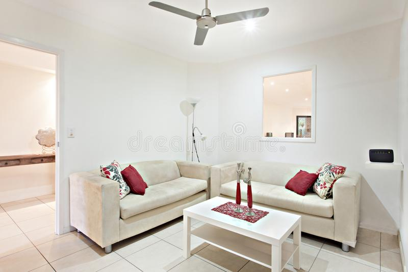 Luxury sofa set near wooden table. Comfortable furnitures with designs, walls are white color, pillows on chairs, inside rooms of a apartment stock images