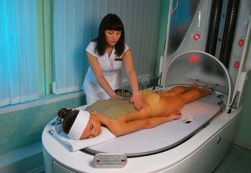 Luxury spa. A sea mud full body wrap being applied to the body at a luxury spa royalty free stock photo