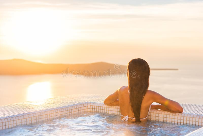 Luxury spa wellness resort woman relaxing in hot tub jacuzzi watching sunset over the Aegean sea in the Cyclades islands,. Santorini, Greece, Europe. Hotel royalty free stock photography